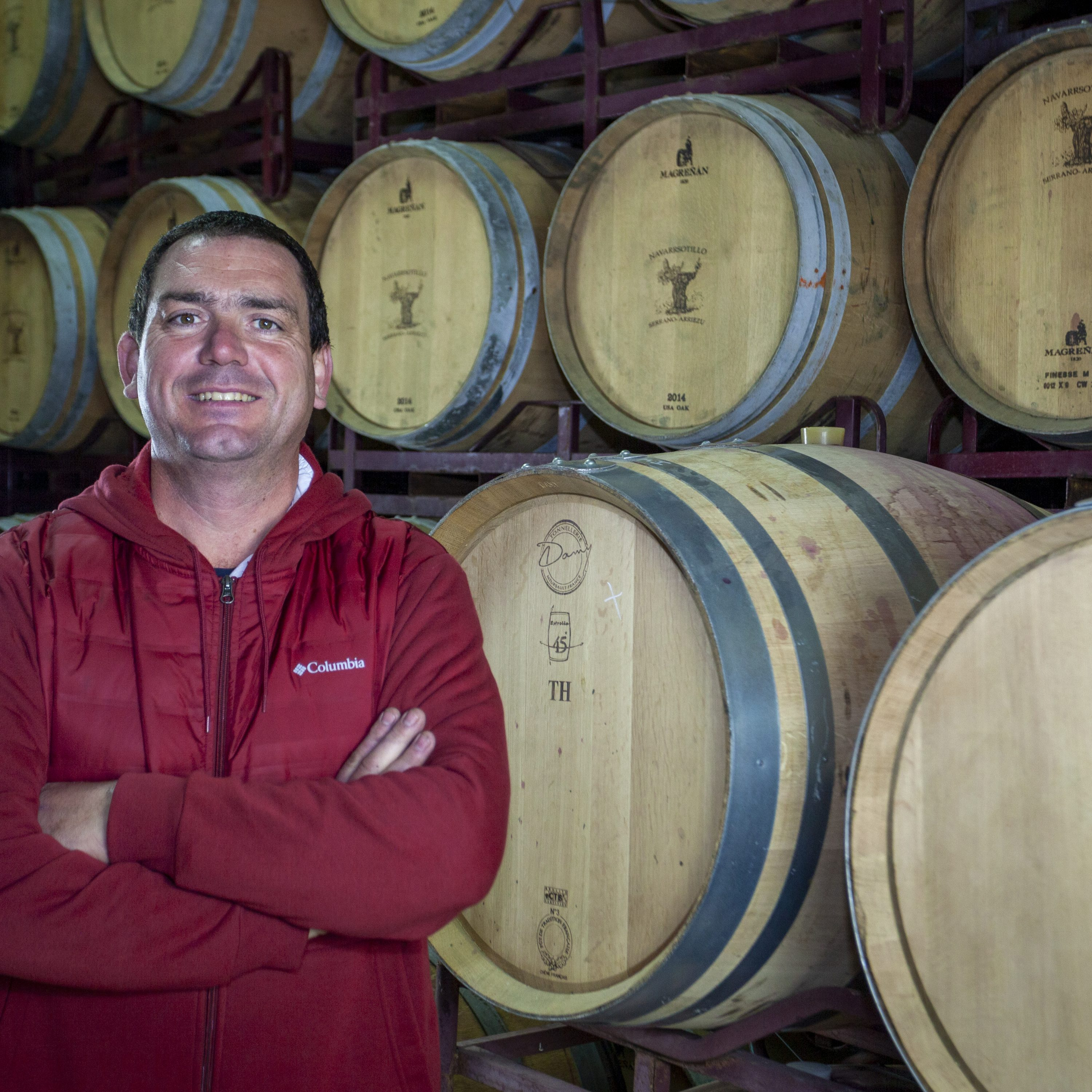 wine maker with wine barrels in background